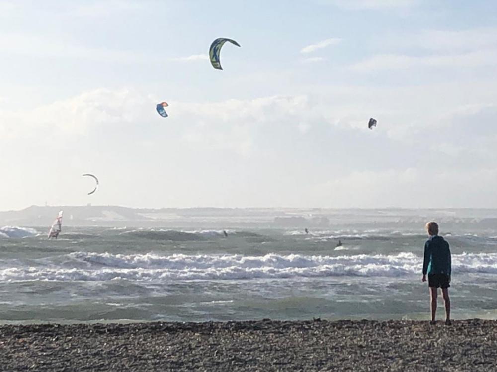 Kiran steht am Strand und beobachtet die Kite-Surfer