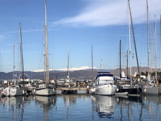 Boote im Hafen und im Hintergrund liegt Schnee auf den Bergen der Sierra Nevada