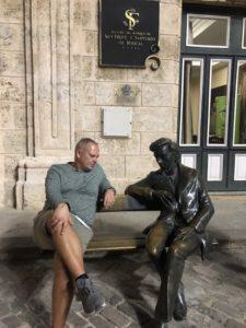 Tom neben einer Bronzestatue auf einer Bank