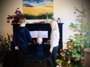 Kiran, der kleine Cousin und Solana am Klavier. Daneben der Weihnachtsbaum