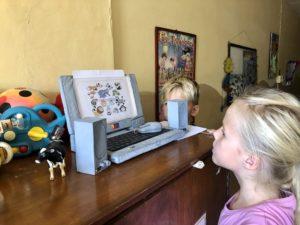 Kiran und Solana betrachten einen Laptop aus Pappmaschee